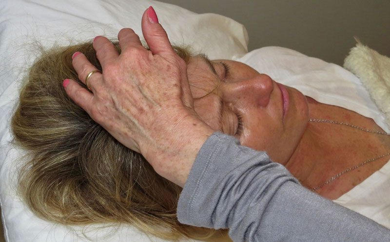 image of someone laying a hand on a forehead