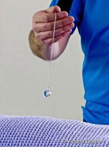 image of crystal pendulum swinging over someone's body