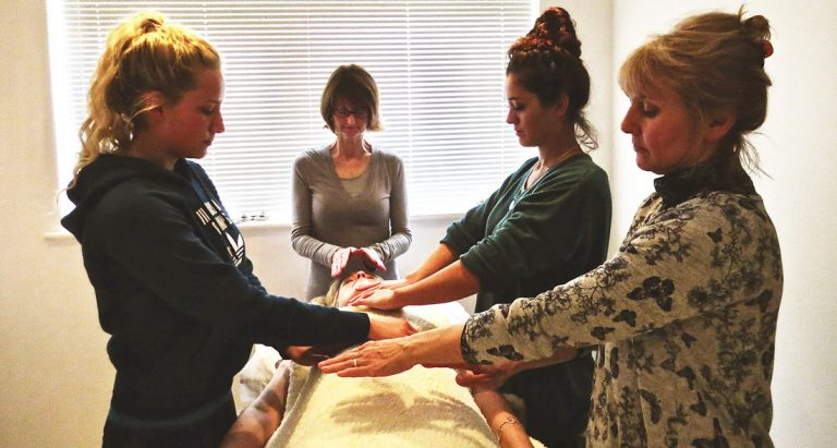 image of 4 ladies giving a reiki treatment